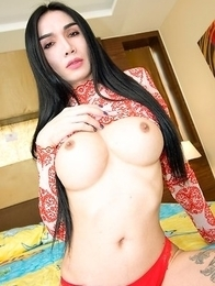 Slim and elegant Ladyboy Bella is wearing a sheer red and white dress. She emerges from the doorway and makes her way to the bed in a seductive fashio