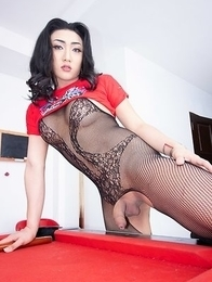 Ladyboy Paeng is sitting on a bar stool wearing a red tshirt and booty shorts over a black body stocking.