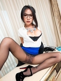 Ladyboy Tata sits on the desk and strokes her cock. Then he has her lie on the desk and he fucks her there on her back.